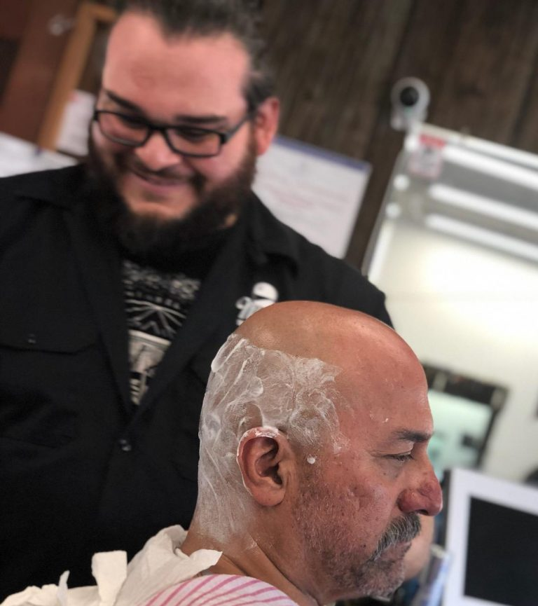 Barber Andre shaving a head at Mike's Barber Shop in Pismo Beach